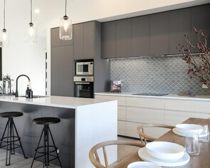 Contemporary black kitchen with black tap and pendant lights
