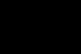 Black kitchen with black stone kitchen bench with rustic tiles for splashback